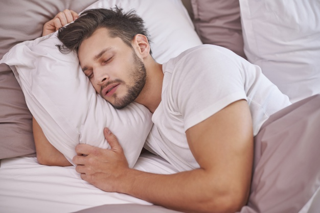 exhausted-man-sleeping-his-bed_329181-3282