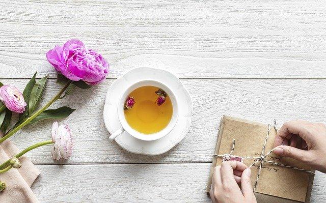 Žena zväzuje hnedé obálky na bielom stole, na ktorom je šálka s čajom a ruže.jpg
