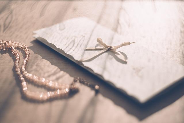 Biela podlhovastá obálka na stole, vedľa ktorej je náhrdelník.jpg
