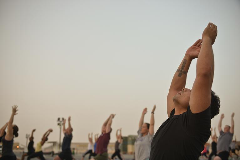 Muž cvičí jogu na pláži s ostatnými ľuďmi.jpg