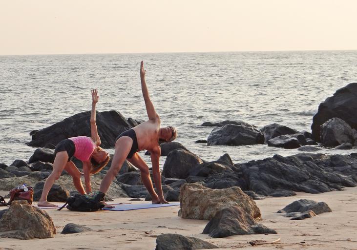 Žena a muž cvičia na pláži na športových podložkách.jpg